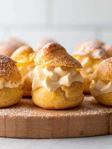 Cream puffs on a board with a powder sugar dusting.