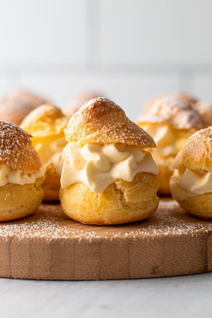 Cream puffs on a board with a powder sugar dusting.