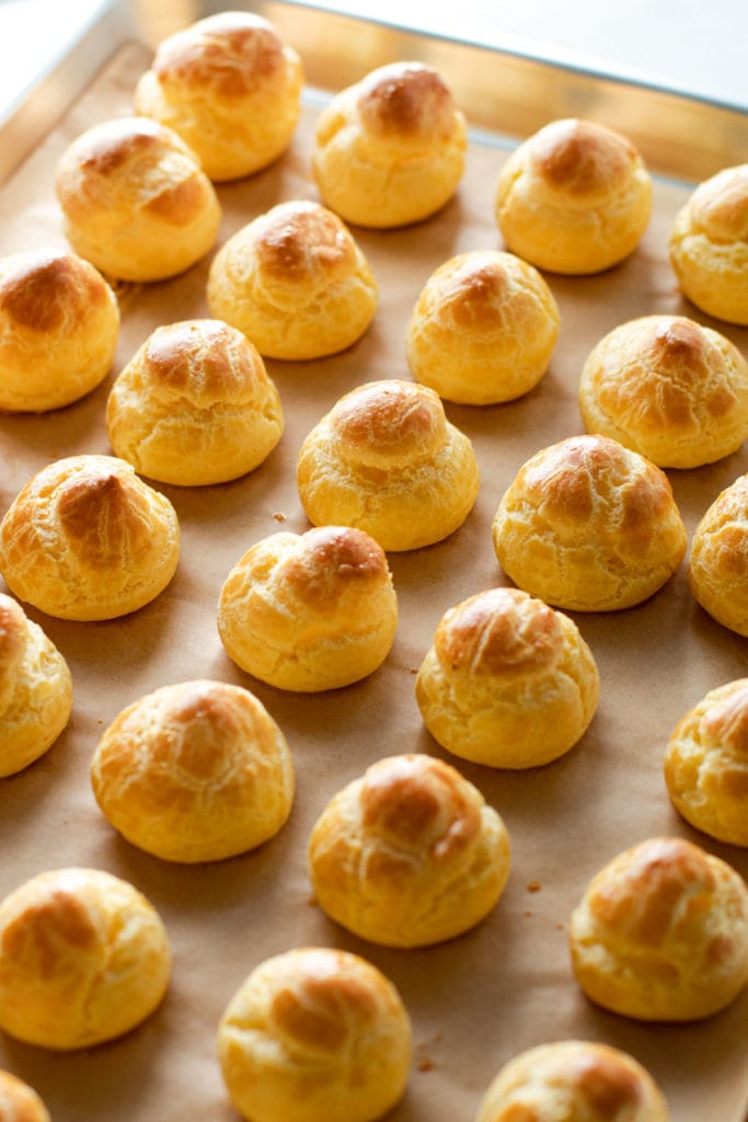 Choux Pastry puffs on a baking tray.