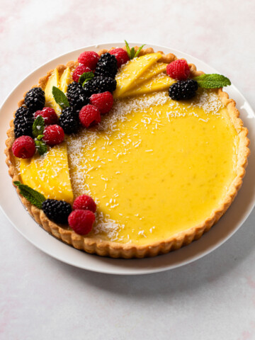 A coconut lime tart with a decorative ring of berries and fruit