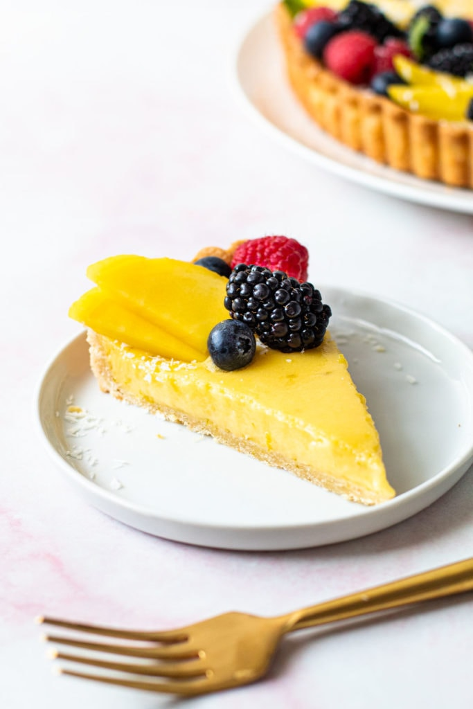 A slice of coconut lime tart with fruit on top.