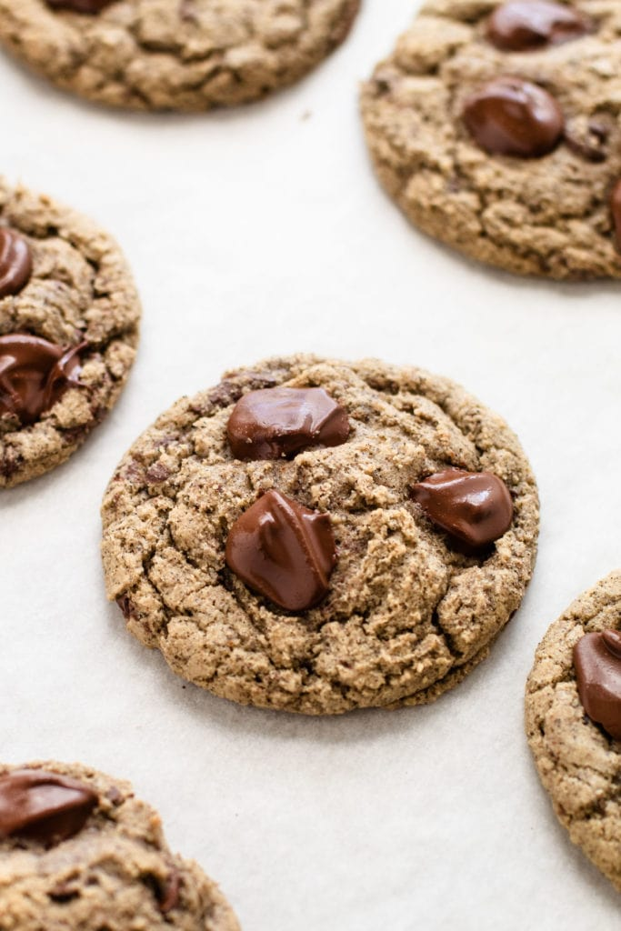 A chocolate chip cookie on a sheet tray, made from oat flour and buckwheat flour.