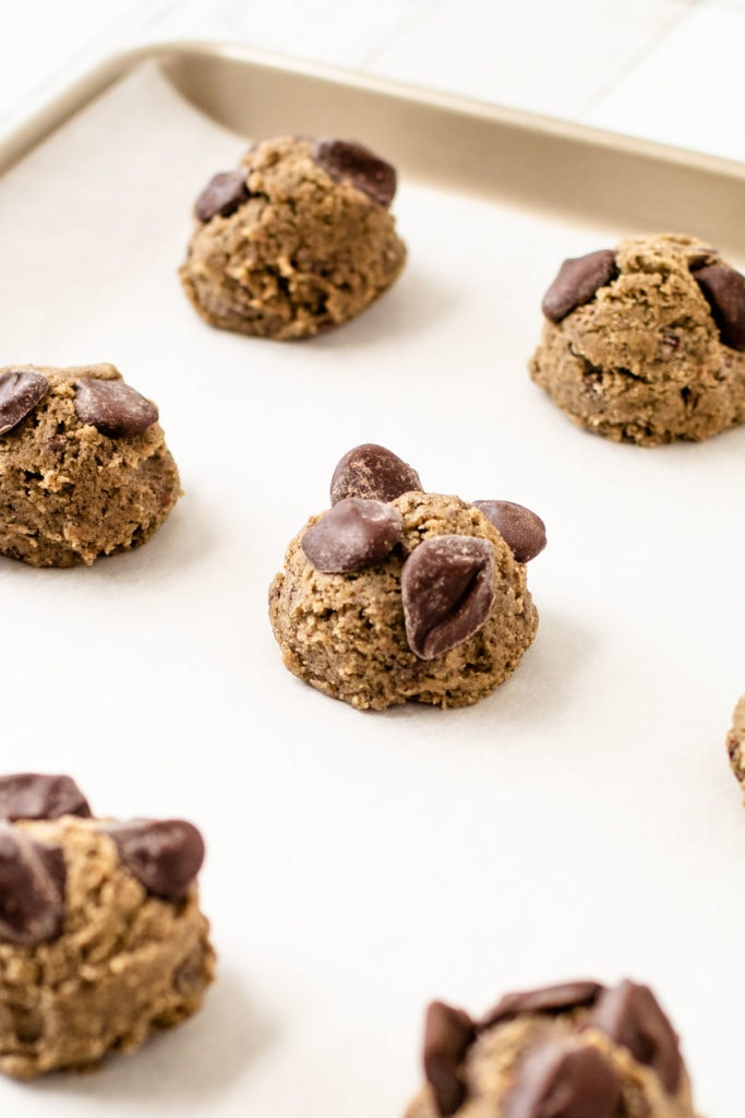 Buckwheat and oat flour chocolate chip cookie batter on a sheet tray.
