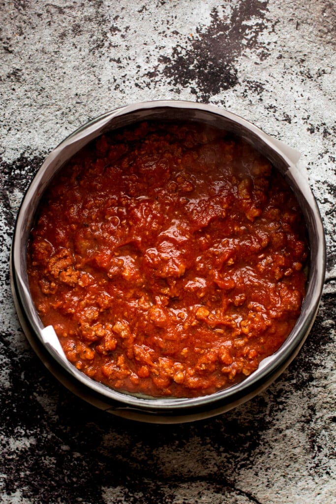 A layer of meat sauce for honeycomb pasta.