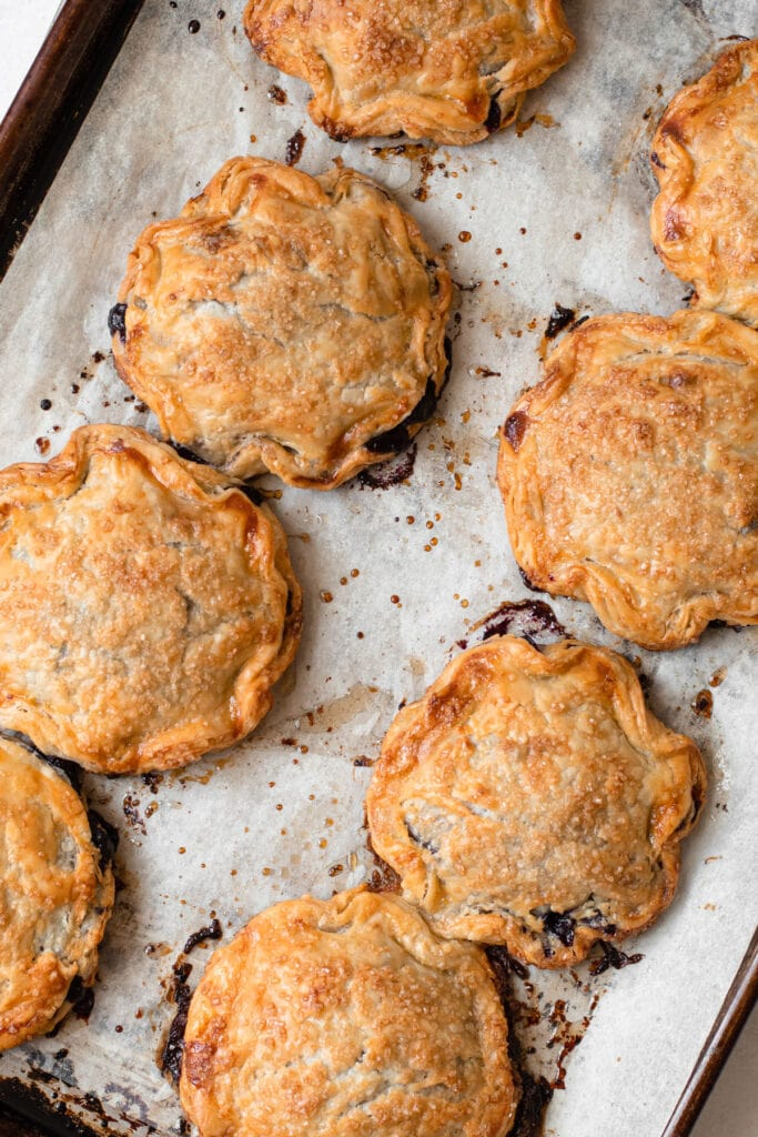 Blueberry hand pies on a baking tray.