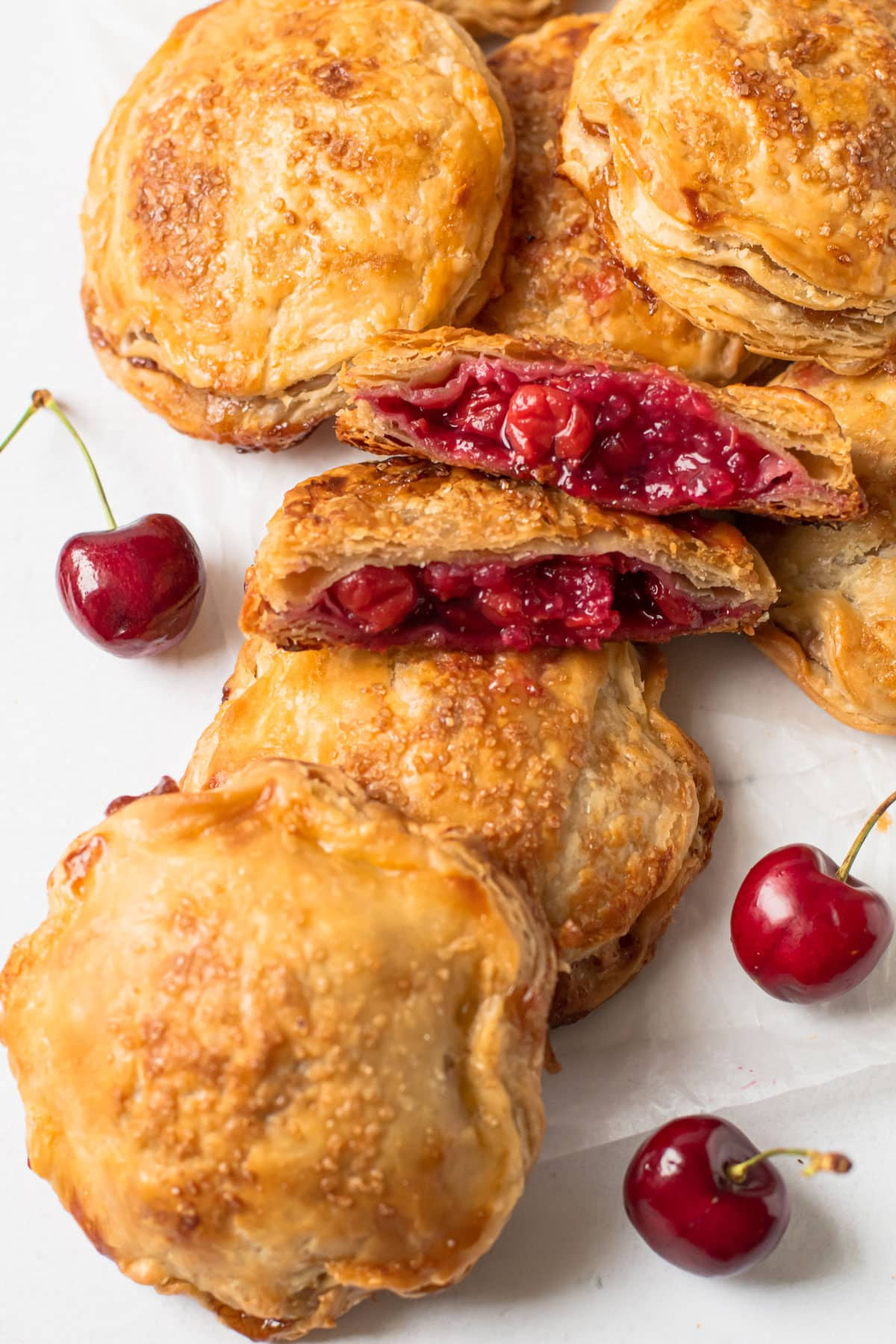 A pile of cherry hand pies with one broken open to reveal the cherry filling.