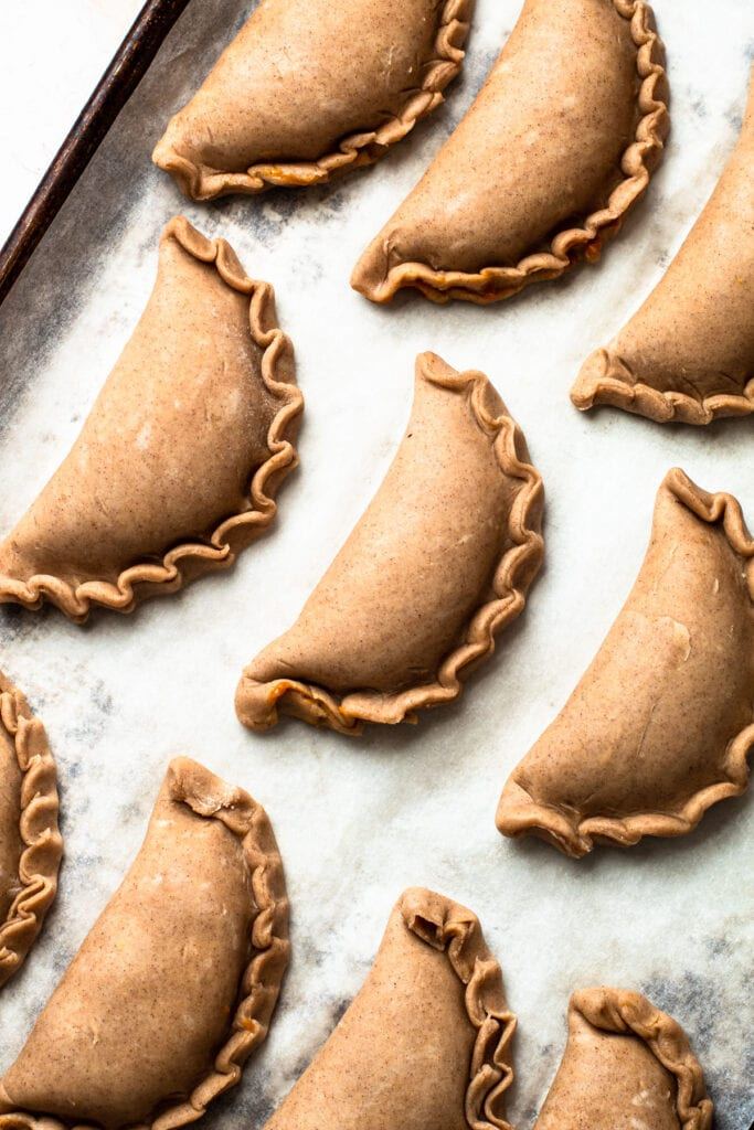 Unbaked pumpkin pasties on a sheet tray.