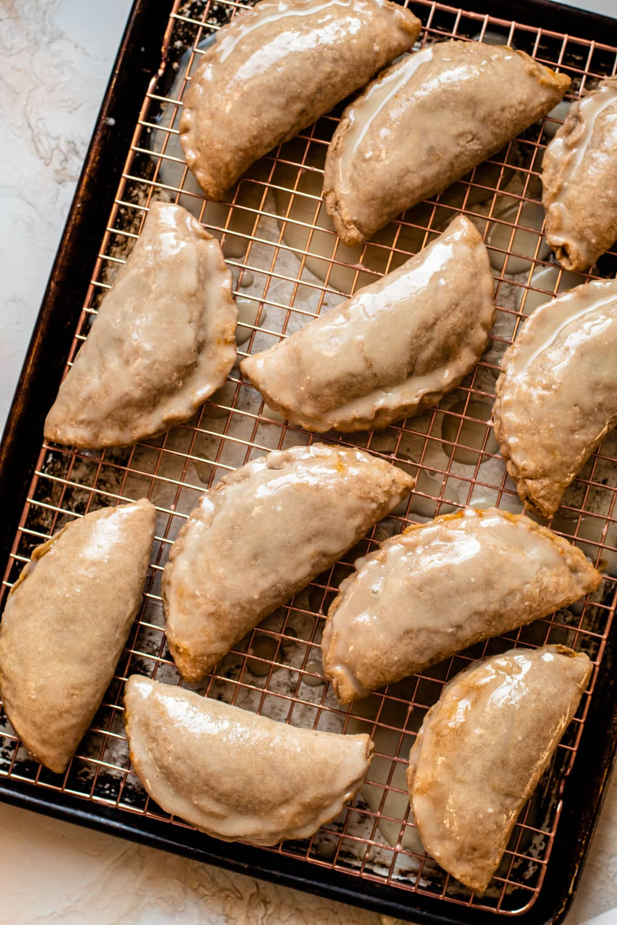 Pumpkin pasties inspired by harry potter sitting glazed on a sheet tray.
